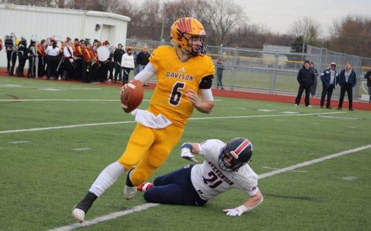 Davison quarterback Brendan Sullivan escapes Sterling Heights Stevenson's Jordan Kwiatkowski in an MHSAA football Division 1 semifinal Nov. 23, 2019, at Troy Athens.