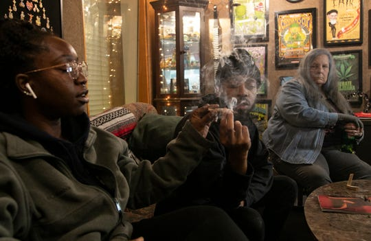 Brittiney (no last name given), left, receives a joint passed by a man who goes by the name of Elevated Yogi as Christeen Landino of Eastpointe looks on during a marijuana social club gathering Friday at an office in Detroit Friday Nov. 22, 2019.