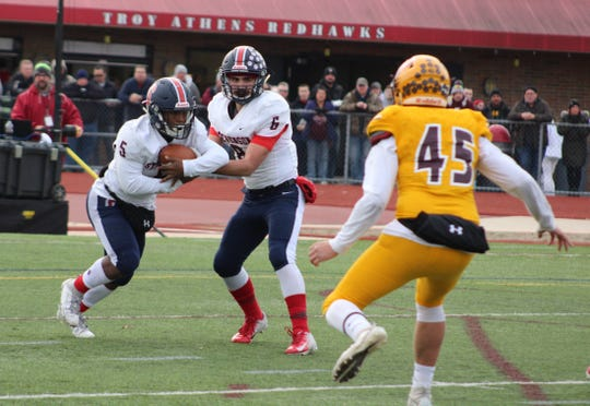 Sterling Heights Stevenson's Jordan Ramsey takes the handoff from quarterback Biagio Madonna in a MHSAA football Division 1 semifinal against Davison on Nov. 23, 2019, at Troy Athens.