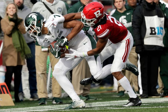 Michigan State wide receiver Cody White (7) makes a catch in front of Rutgers defensive back Tre Avery during the first half.