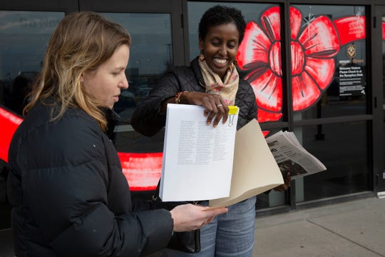 In this Wednesday, Nov. 20, 2019 photo, from left, Mary Blitzer, of the Sierra Club, gives a petition of over 23,000 signatures to Amira Adawe of the Beautywell Project as they deliver it to the Amazon Fulfillment Center in Shakopee, Minn.