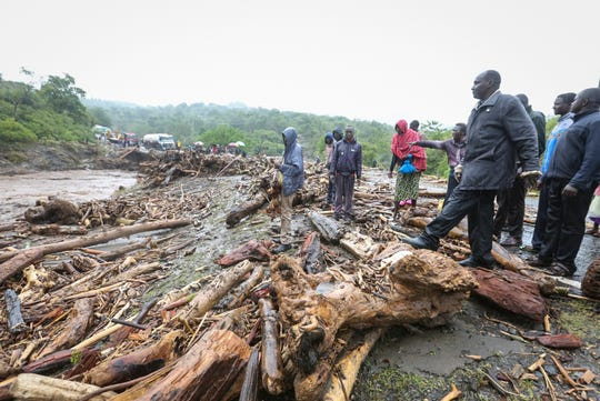 Passengers from stranded vehicles stand next to the debris from floodwaters, on the road from Kapenguria, in West Pokot county, in western Kenya Saturday, Nov. 23, 2019. Kenya's interior minister says dozens of people have been killed in mudslides, after heavy rains unleashed overnight floods in western Kenya. (AP Photo)