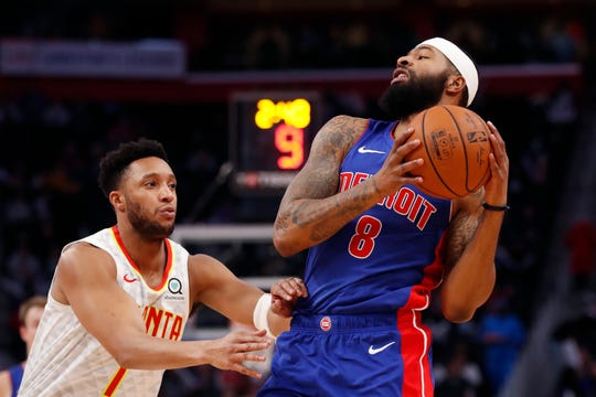 Pistons forward Markieff Morris catches a pass as Hawks guard Evan Turner defends.