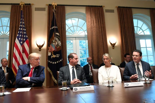 President Donald Trump, second from left, listens to American Vaping Association President Greg Conley, right, during a meeting in the Cabinet Room of the White House in Washington, Friday, Nov. 22, 2019, on youth vaping and the electronic cigarette epidemic. Sitting at the table in between them are Health and Human Services Secretary Alex Azar and Kentucky State Sen. Julie Raque Adams. (AP Photo/Susan Walsh)