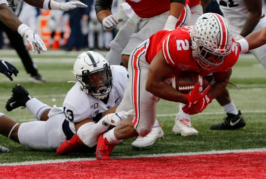 Ohio State running back J.K. Dobbins, right, drags Penn State linebacker Ellis Brooks into the end zone for a score during the first half on Saturday.