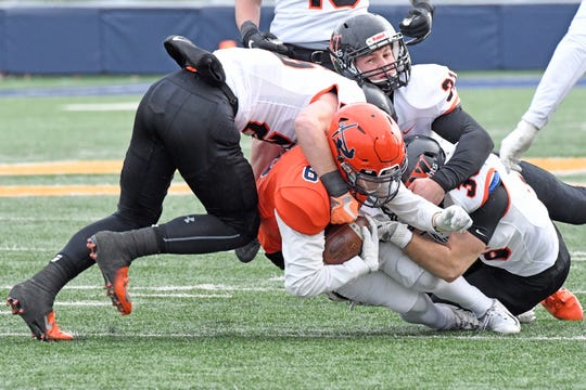 A Hope College ball carrier gets brought down by Wartburg defenders in Saturday's Division 3 NCAA playoff game.