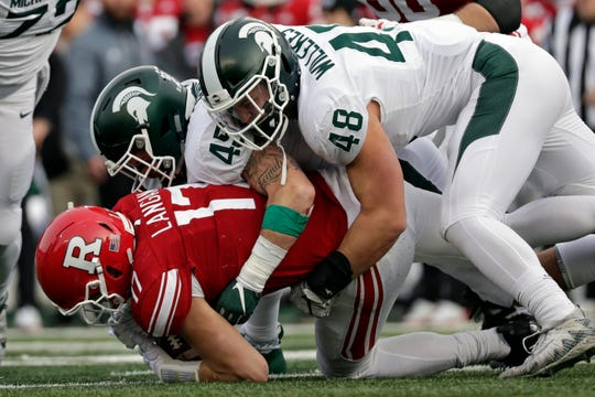 Rutgers quarterback Johnny Langan (17) is sacked by Michigan State defensive end Kenny Willekes (48) and linebacker Noah Harvey (45) during the second half  on Saturday.