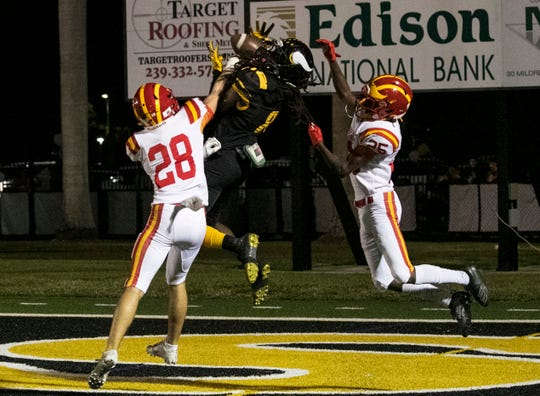 Malik Curtis of Bishop Verot catches a touchdown pass between 	Brad Seale and Nate Johnson of Clearwater Central Catholic in the Class 3A regional final game on Friday, Nov. 22, 2019, at Bishop Verot High School in Fort Myers.