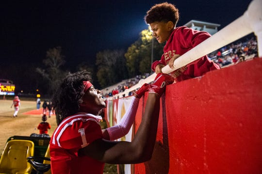 Greenville's Jalen Tate (1) talks to his little brother Jayven Rice, 8, during halftime in their game against Wren Friday, November 22. 2019. Wren won their third round playoff game 17-7.