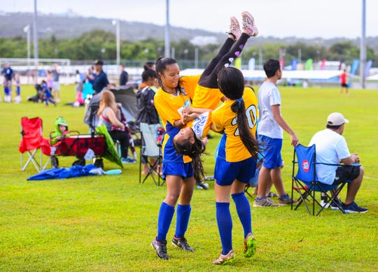 Aurielle Dulla, 6, gets a friendly flip on the sidelines by sister, Kaeli Flores, left, and friend, Jasani Taylor during the Triple J Auto Group Robbie Webber Youth League 2019 Fall Season Jamboree at the Guam Football Association National Training Center in Dededo on Saturday, Nov. 23, 2019.
