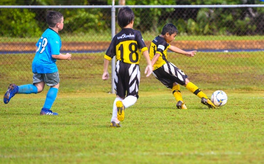 Napa Rovers-Yellow's Miguel Paxtian, 8, sweep kicks the ball into the goal during the Triple J Auto Group Robbie Webber Youth League 2019 Fall Season Jamboree at the Guam Football Association National Training Center in Dededo on Saturday, Nov. 23, 2019.