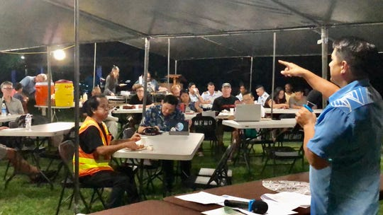 Jesse Cruz, environmental monitoring and analytical services administrator for the Guam Environmental Protection Agency, gestures as he addresses a crowd Friday night at the Merizo Pier Park about the planned removal early next year of some 2,500 used tires from the Cocos Lagoon.
