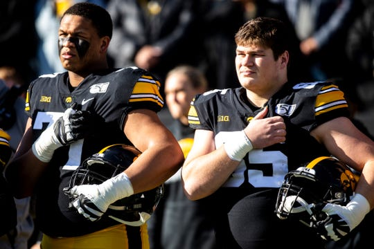 Iowa offensive tackle Alaric Jackson (left, next to Tyler Linderbaum during the national anthem Nov. 23) is apparently not considering heading to the NFL a year early. That's potentially big news for the Hawkeyes' 2020 chances to compete for a Big Ten West title.