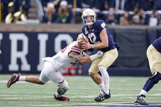 Notre Dame quarterback Ian Book (12) is hit by Boston College linebacker Isaiah McDuffie (55) as he throws.