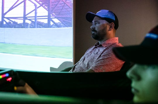 Former Formula One and IndyCar driver Darren Manning watches Michael Myers train on an iRace simulator at a training facility off of Guion Road, Indianapolis, Nov. 6, 2019.