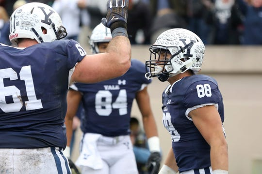 FILE - In this Nov. 18, 2017, file photo, Yale's JP Shohfi, right, celebrates with teammates after scoring a first half touchdown against Harvard during an NCAA college football game in New Haven, Conn. Yale quarterback Kurt Rawlings has rewritten the school's record books for passing, throwing the ball to Shohfi and Reed Klubnik, who he convinced to come with him to the Ivy League. (AP Photo/Gregory Payan, File)
