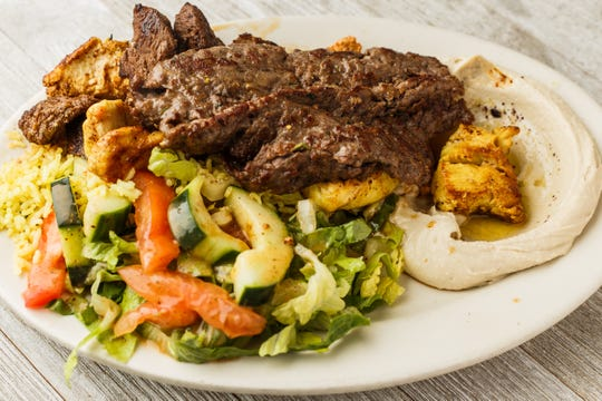 Aladdin's combo kabab plate is filled with a variety of grilled meats, green salad, rice and hummus.