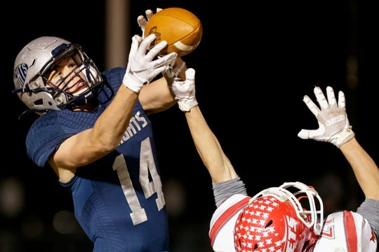 Central Catholic's Ky Schrader (14) catches a pass over Adams Central's Alex Currie (21) during the third quarter of the IHSAA class A semi-state football game, Friday, Nov. 22, 2019 in Lafayette. Central Catholic won, 24-14.