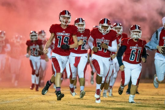 Comeaux High runs onto the field to start the game as the Comeaux High Spartans take on the Haughton High Buccaneers on Friday, Nov. 22, 2019.