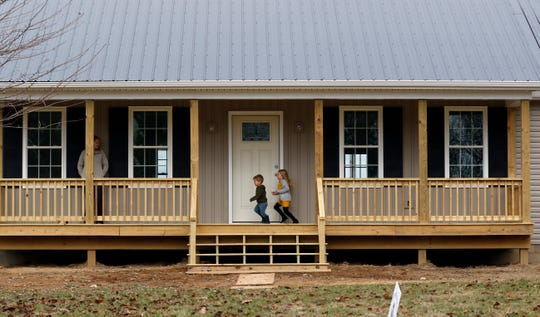 Luke Smith, center, races his older sister Layla Smith, right, across the front porch of their new home while their mother Molly Smith, left, watches them Saturday, Nov. 23, 2019, in Rushcreek Township. The family hopes to move into their new home before Christmas, less than a year after their home was destroyed by a fire.