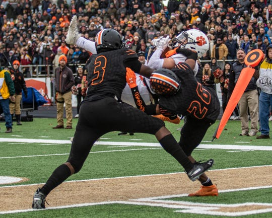 Brighton's Nick Nemecek hauls in the game-winning touchdown pass between Belleville's Jalen Williams (3) and Deshaun Lee (26) with 50.1 seconds left in a state Division 1 football semifinal at Howell on Saturday, Nov. 23, 2019.