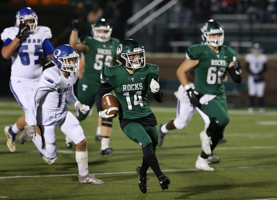 Trinity's Bradley West (14) got a huge run against Oldham County during their game at Trinity High School in Louisville, Ky. on Nov. 22, 2019.  His run set up a touchdown play.