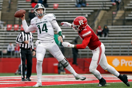 Michigan State quarterback Brian Lewerke (14) passes under pressure from Rutgers defensive lineman Tijaun Mason (91 during the second half of an NCAA college football game Saturday, Nov. 23, 2019, in Piscataway, N.J. Michigan State won 27-0. (AP Photo/Adam Hunger)