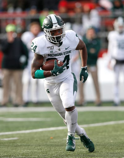 Nov 23, 2019; Piscataway, NJ, USA; Michigan State Spartans running back Elijah Collins (24) rushes against the Rutgers Scarlet Knights during the second half at SHI Stadium. Mandatory Credit: Noah K. Murray-USA TODAY Sports