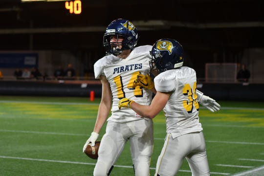 Pewamo-Westphalia senior Aaron Bearss (14) celebrates with a teammate during the Pirates' Division 7 state semifinal victory over Iron Mountain on Friday, Nov. 23, 2019, in Marquette.