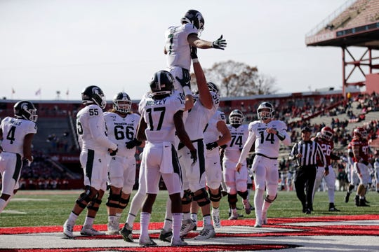 Michigan State wide receiver Cody White is lifted by offensive lineman Nick Samac after scoring a touchdown against Rutgers during the first half of an NCAA college football game Saturday, Nov. 23, 2019, in Piscataway, N.J. (AP Photo/Adam Hunger)