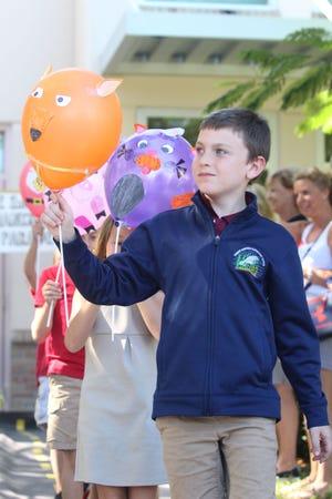 CJ Quinton proudly shows off his orange fox balloon.