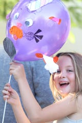 "Cecillia Dunn gleaming with her purple ""Caticorn"" balloon."