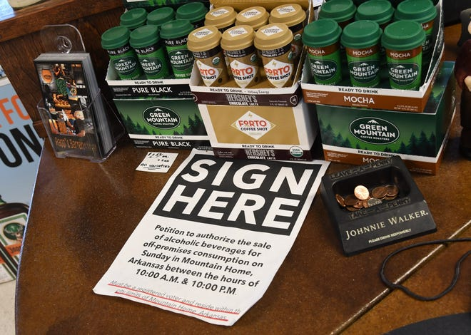 A sign advertising a local petition to authorize the sale of off premise alcohol on Sundays sits on the counter of Midtown Spirits earlier this month. Mountain Home voters will decide in March whether to allow such sales, which are already allowed in Norfork, Salesville and parts of Marion County.