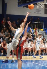 Cotter's Hayden Hutson puts up a shot while being fouled against Green Forest on Friday night.