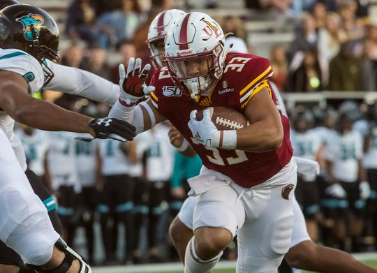 University of Louisiana at Monroe's Austin Vaughn (33) carries the ball for a 10 yard touchdown during the game against Coastal Carolina University at Malone Stadium in Monroe, La. on Nov. 23.
