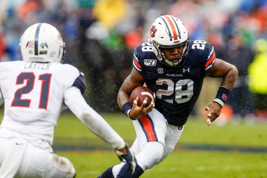 Auburn running back JaTarvious Whitlow (28) carries the ball as he tries to get past Samford defensive back Joshua Carter (21) during the first half of an NCAA college football game, Saturday, Nov. 23, 2019, in Auburn, Ala. (AP Photo/Butch Dill)