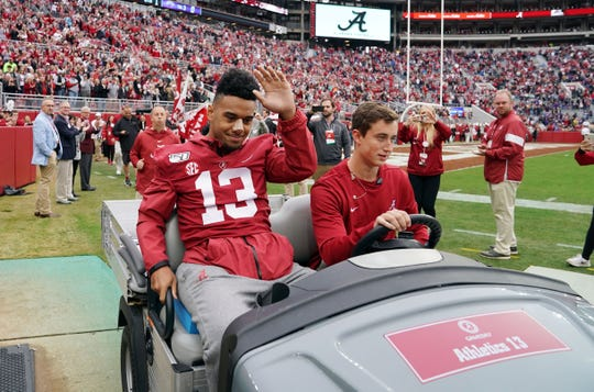 Nov 23, 2019; Tuscaloosa, AL, USA; Alabama Crimson Tide quarterback Tua Tagovailoa (13) waves to the crowds as he is carted onto the field before the start of their game against the Western Carolina Catamounts at Bryant-Denny Stadium. Tagovailoa also suffered a posterior wall fracture at last weeks Mississippi State game. Mandatory Credit: John David Mercer-USA TODAY Sports