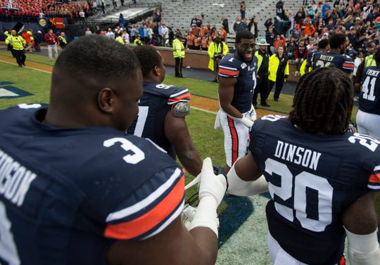Auburn defensive lineman Big Kat Bryant (1) and Auburn defensive lineman Marlon Davidson (3) joke as they walk off the field  at Jordan-Hare Stadium in Auburn, Ala., on Saturday, Nov. 23, 2019. Auburn defeated Samford 52-0.