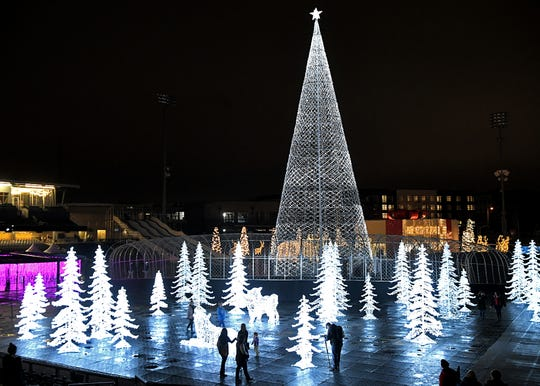 Glow Nashville is a holiday display located on the Sounds' baseball field at First Tennessee Park featuring ice skating, ski-tile tube park, and a 100-foot-tall LED Christmas tree. People walk around the holiday sculptures at First Tennessee Park on Friday, Nov. 22, 2019.