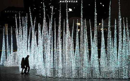 People walk around the holiday sculptures at Glow Nashville, a holiday display located on the Sounds' baseball field at First Tennessee Park featuring ice skating, ski-tile tube park, 100-foot-tall LED Christmas tree.