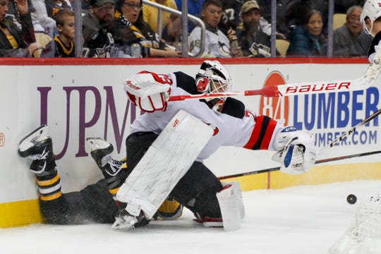 New Jersey Devils goaltender Mackenzie Blackwood, right, and Pittsburgh Penguins' Brandon Tanev collide behind the goal chasing the puck during the second period of an NHL hockey game, Friday, Nov. 22, 2019, in Pittsburgh.