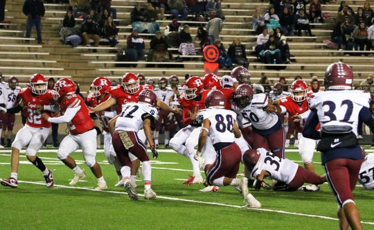 The Deming High defense (in white) had to contend with Roswell's  no-huddle offense and the fastest team they had faced all season.