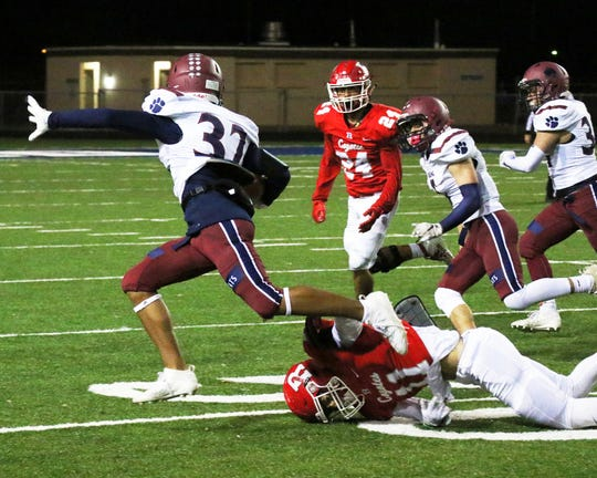 Junior Jordan Caballero (32) looks for daylight during Friday's Class 5A semi-final playoff against Roswell.