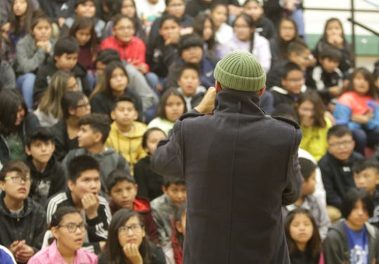 Newcomb Middle School students watch Christopher Mike-Bidtah's performance at the Falcon Poetry Slam on Nov. 22 in Newcomb.