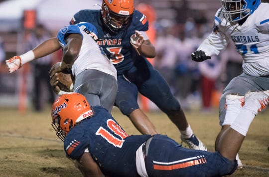 KD Teamer (10) and Xavier Johnson (13) take down Cobie Bates (6) during the Lee vs Escambia playoff football game at Escambia High School in Pensacola on Friday, Nov. 22, 2019.