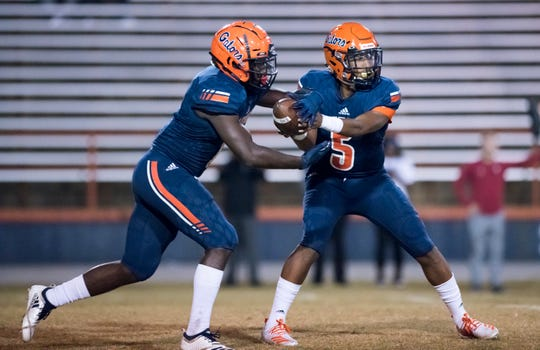 Quarterback AV Smith (5) hands off during the Lee vs Escambia playoff football game at Escambia High School in Pensacola on Friday, Nov. 22, 2019.