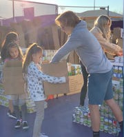 Northwest Christian students fill boxes of canned goods for the Sutton Project in Phoenix.