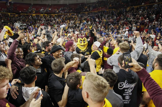 Arizona State University students storm the mat after their Sun Devils upset win over #1 Penn State at Desert Financial Arena in Tempe , Friday, Nov. 22, 2019.