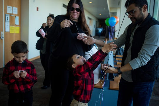 David Lewis, left, and Ezrah Lewis, center play with a family member while Collen Sbarboro, their adoptive mother's fiancee, takes a photo of them during Maricopa County's National Adoption Day Celebration, where over 140 children formerly in foster care had their adoptions finalized Saturday, Nov. 23, 2019, at Durango Juvenile Court Center in Phoenix.
