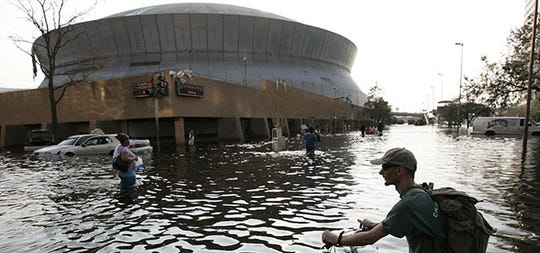 A man pushes his bicycle through flood waters near the Superdome in New Orleans on Aug. 31, 2005.